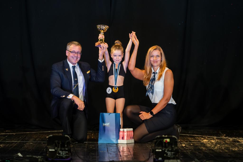 President Ergo Metsla ja peasekretär Janika Koch-Mäe koos 6-aastaste Eesti laste fitnessi meistri Eliis Räitsakuga